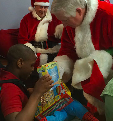 Happy Santas volunteer distributing gift to child